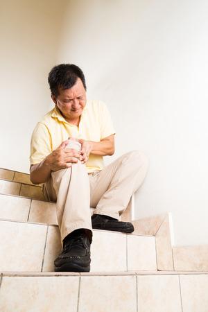 dolor de rodilla: Hombre Madurado sufrir dolor en las articulaciones de rodilla aguda sentado en la escalera
