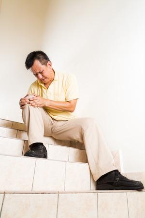 artritis: Hombre Madurado sufrir dolor en las articulaciones de rodilla aguda sentado en la escalera