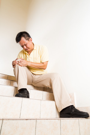 knees: Matured man suffering acute knee joint pain seated on staircase Stock Photo