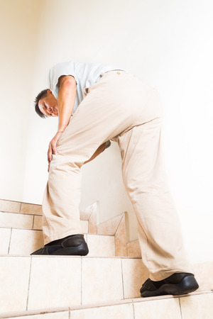 acute: Matured man suffering acute knee joint pain climbing staircase Stock Photo