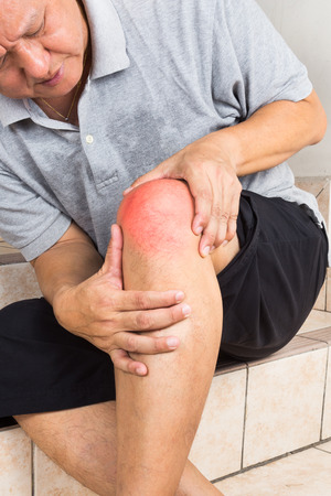 knee: Matured man suffering from painful knee joint resting on steps