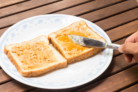 peanut butter and jelly: Hand spreading peanut butter and jelly onto wholemeal bread