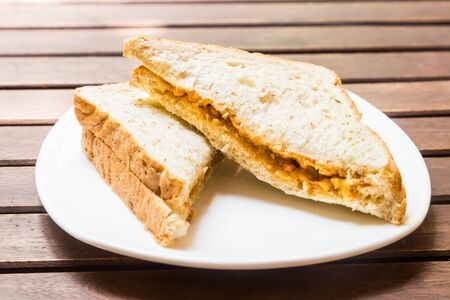 peanut butter and jelly sandwich: Wholemeal sandwich bread spread with peanut butter and jelly served on plate outdoor