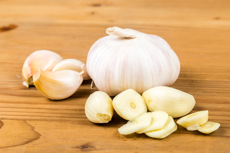 fresh garlic: Peeled and sliced garlic cloves with whole garlic bulb and cloves as background Stock Photo