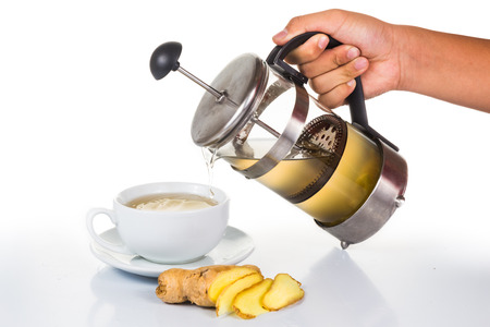 tea filter: Hand pouring ginger tea into cup from filter jar