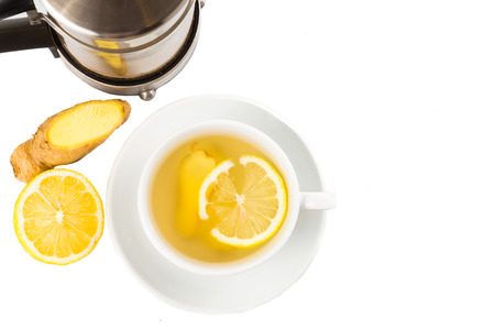 stimulating: Hot ginger and lemon tea in a cup and filter jar Stock Photo