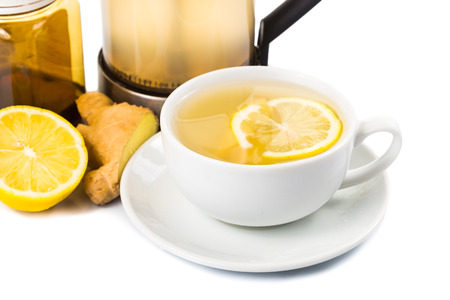 Hot honey ginger and lemon tea in a cup and filter jar photo