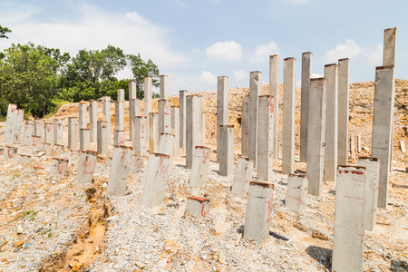 cement pole: Piling concrete columns pounded into ground at construction site