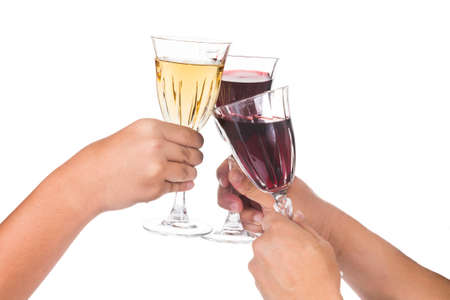 cabernet sauvignon: Hands toasting red and white wine in crystal glasses