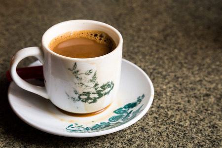 ambient light: Traditional oriental Chinese coffee in vintage mug and saucer in soft focus setting with ambient light Stock Photo