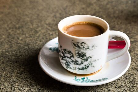 kopitiam: Traditional oriental Chinese coffee in vintage mug and saucer in soft focus setting with ambient light Stock Photo