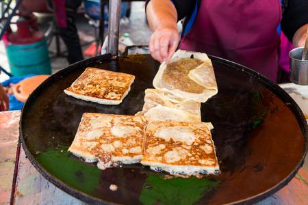 catered: Vendor preparing traditional murtabak cuisine at street bazaar in Malaysia catered for iftar during Muslim fasting month of Ramadan