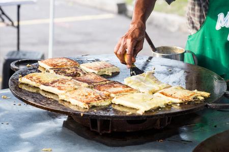 Vendor preparing traditional murtabak cuisine at street bazaar in Malaysia catered for iftar during Muslim fasting month of Ramadan