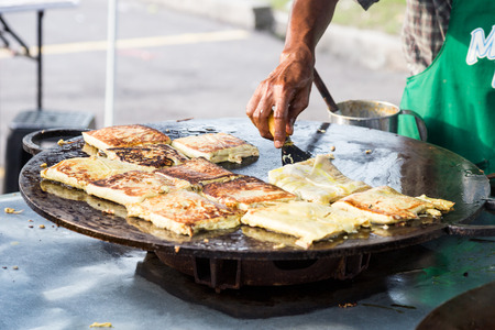 Vendor preparing traditional murtabak cuisine at street bazaar in Malaysia catered for iftar during Muslim fasting month of Ramadan