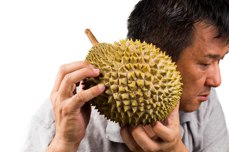 ripeness: Man hold and shake durian fruit to assess its ripeness