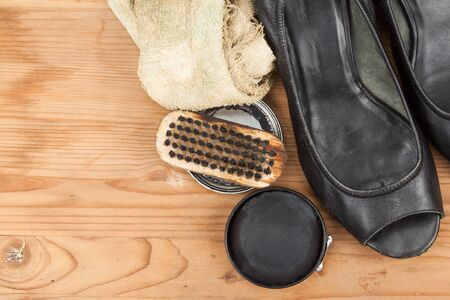 shoes woman: Shoe polish with brush, cloth and worn ladies court shoe on wooden platform. Stock Photo