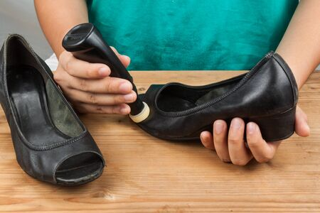 restoring: Person polishing and restoring worn out shoe with liquid shoe polish.