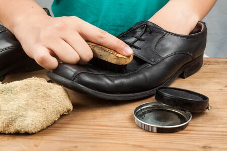 restoring: Person polishing and restoring worn out mens formal shoes.