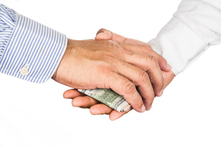 corruption: Hand shake deal with corrupt cash exchange.