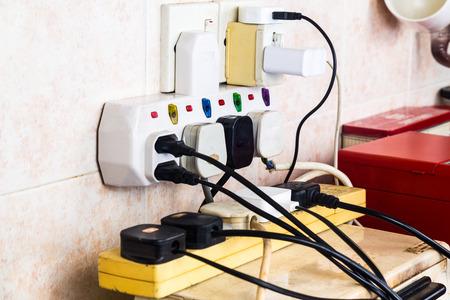 peligro: Enchufes de electricidad múltiples en sobrecarga riesgo adaptador y peligroso. Foto de archivo