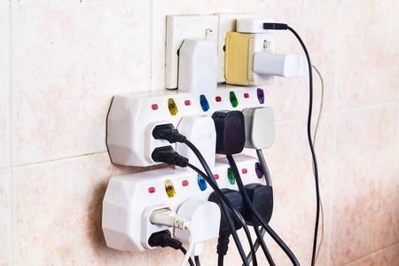 peligro: Enchufes de electricidad m�ltiples en sobrecarga riesgo adaptador y peligroso. Foto de archivo