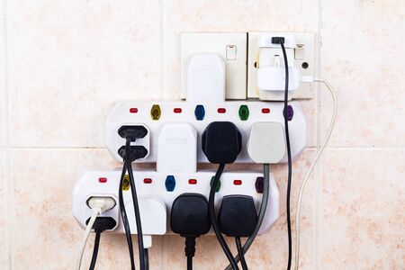 overloading: Multiple electricity plugs on adapter risk overloading and dangerous. Stock Photo