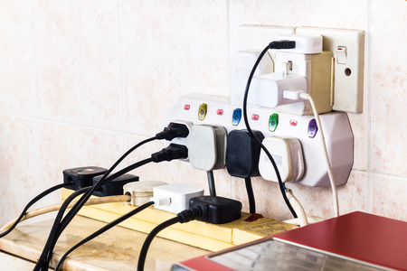 overloaded: Multiple electricity plugs on adapter risk overloading and dangerous. Stock Photo