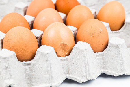 cracked: One egg with cracked egg shell with other eggs on tray Stock Photo