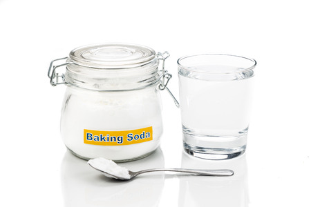 bicarbonate: Baking soda in jar, spoonful and glass of water for multiple holistic usages.