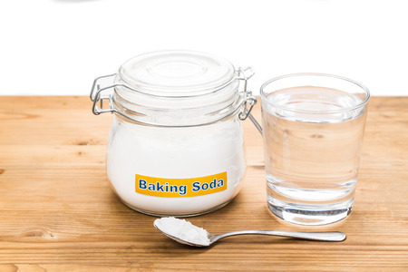 spoonful: Baking soda in jar, spoonful and glass of water for multiple holistic usages.