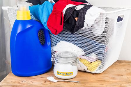 productos naturales: El bicarbonato de sodio con detergente y la pila de ropa sucia