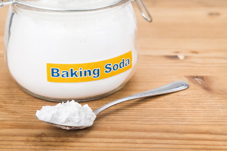 baking: Jar and spoonful of baking soda for multiple holistic usages. Stock Photo