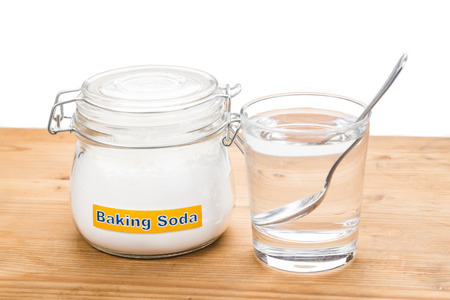 baking: Baking soda in jar, spoonful and glass of water for multiple holistic usages.