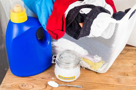 Baking soda with detergent and pile of dirty laundry Stock Photo