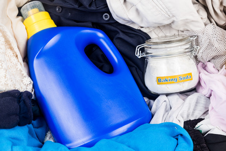baking: Closeup on baking soda with detergent and pile of dirty laundry Stock Photo