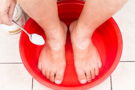 holistic care: Baking soda being used as feet bath at home Stock Photo
