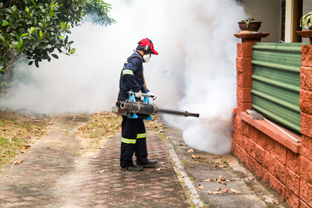Worker fogging residential area with insecticides to kill aedes mosquito, carrier of dengue virus Archivio Fotografico