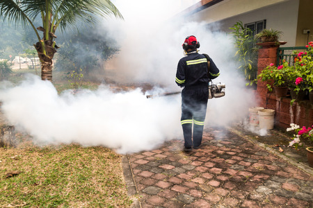 Worker fogging residential area with insecticides to kill aedes mosquito, carrier of dengue virus Редакционное