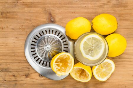 juice squeezer: Freshly squeezed organic lemon juice with glass and squeezer
