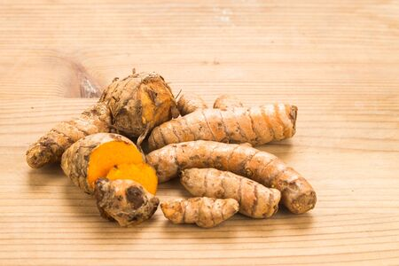 curcumin: Fresh turmeric roots with wellness properties on wooden surface