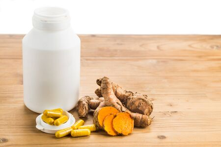 capsules: Homemade turmeric capsule from freshly grounded turmeric roots Stock Photo