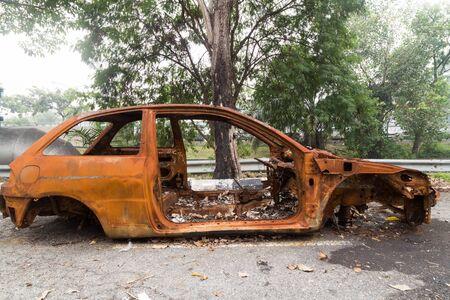 ferraille: Rusty châssis d'une voiture brûlée abandonnée par le côté de la rue