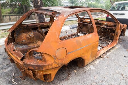 chassis: Rusty chassis of a burnt car abandoned by the side of the street Stock Photo