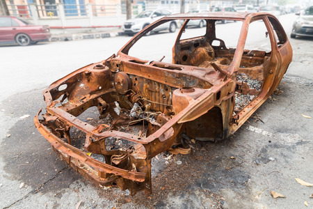 abandoned car: Rusty chassis of a burnt car abandoned by the side of the street Stock Photo