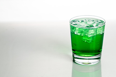 fizzy: Refreshing green fizzy soft drink with ice in transparent glass. Stock Photo