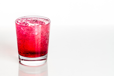 Refreshing red fizzy soft drink with ice in transparent glass.