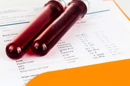screening: Blood sample in test tubes with health analysis screening report. Stock Photo