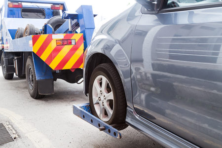 Tow truck towing a broken down car on the street.