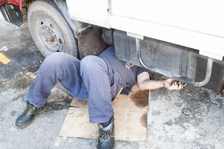 Mechanic under truck reparing dirty greasy oily engine with problem.