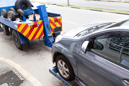 road assistance: Tow truck towing a broken down car on the street.